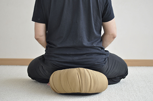 "According to Buddhist precepts, the correct meditation position is called the 'Seven Points Position'. Without going into too much detail, one of the Seven Points advises to ""place the feet with the legs bent in the Buddha's posture"". To do this, the hips should be rotated forward to prevent excessive strain on the knees and damage to the knees. This can be made easier by the use of a meditation cushion that will facilitate this rotation of the hips. Beginners in meditation will start with a meditation cushion that is high enough. With practice, the hips will soften and the height of the meditation cushion can decrease.  This way, the meditator is well installed and predisposes himself to prolonged meditation. In a sitting position, the meditator can sit in the so-called Boddhisatva posture (legs bent in front), in the Vajra or Diamond posture (legs bent and crossed on the thighs, ideal position) or with the legs bent to the side, on either side of the meditation cushion. The meditation posture is according to each person's wishes, well-being and comfort. The position should not be too demanding to avoid injury, but not too comfortable to avoid drowsiness.  Please note that during your meditation sessions, your body cools down considerably, which is why you can use meditation shawls to maintain your body temperature.  Take care to choose your meditation equipment: meditation cushion, mat, blanket, etc. and make sure you invest in quality equipment, it is for your health!"